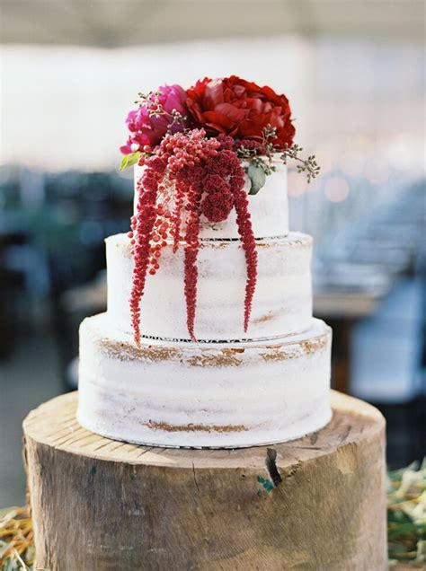 rustic rough frosted wedding cake  crimson flowers