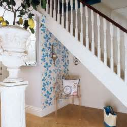 Small hallway with white banisters wood flooring and blue wall