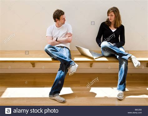 two people sitting on a bench two young people teenage students sitting on bench talking