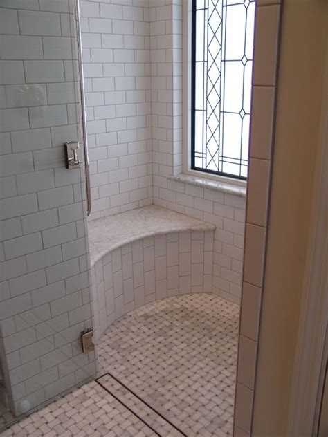 beautiful shower with carerra marble basketweave floor stained glass window and white ceramic