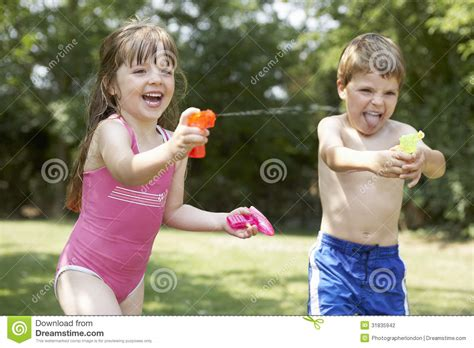 two women fighting in the backyard cheerful kids shooting water pistols stock photography