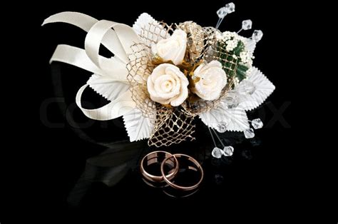 boutonniere and golden wedding rings isolated on a black
