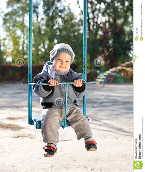 age for baby swing at park baby boy playing on swing in autumn park stock image