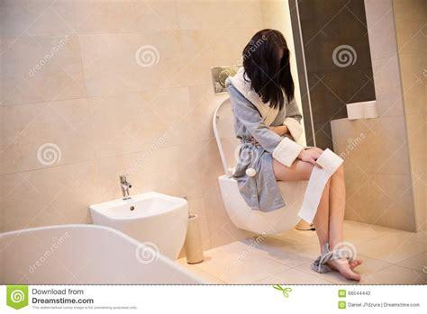 woman bathroom brunette woman sitting on toilet in the bathroom stock