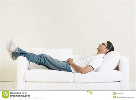 man on the couch indian guy daydreaming stock photo image of business