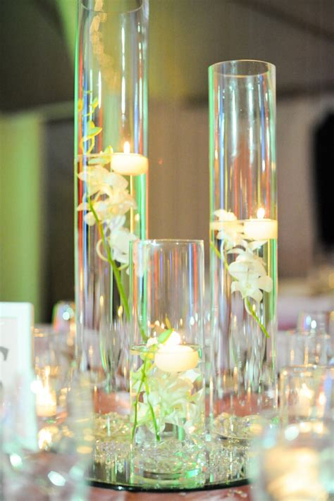 hurricane vases with floating candles and flowers onewed