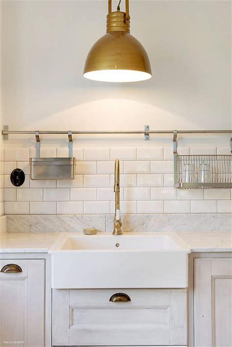 brass fixtures farmhouse sink subway tiles marble countertops brass bar  hanging kitchen