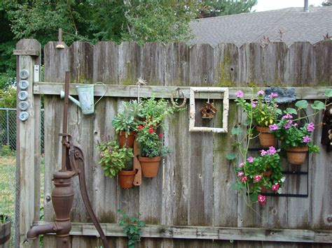 Backyard Fence Decorating Ideas And Rustic Backyard Garden Fence Decoration With Vertical Hanging Planter Pots Ideas