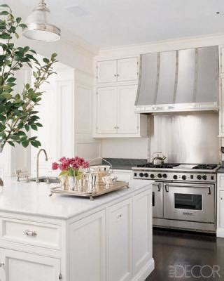 small white kitchen with steel hood french range hood transitional kitchen elle decor