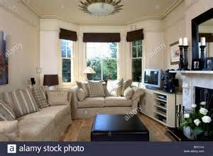 living room bay window beige sofas in cream living room with black blinds on bay window and stock photo royalty free