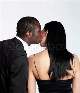 a black man kissing his caucasian wife | stock photo