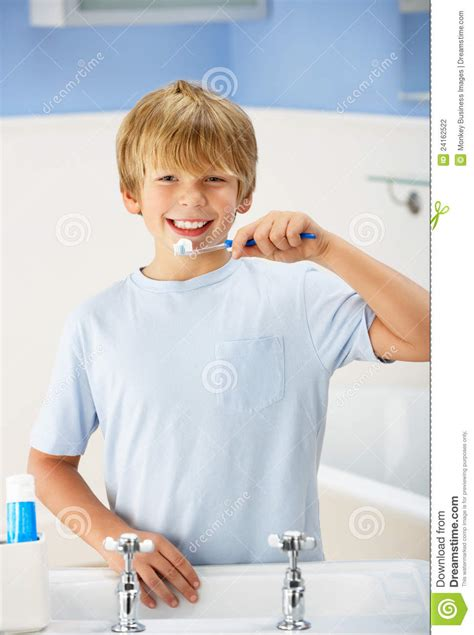 boy cleaning teeth in bathroom stock photography image