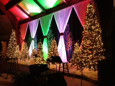 christmas stage decoration black fabric white fabric curtains with different colored up lights tree branches