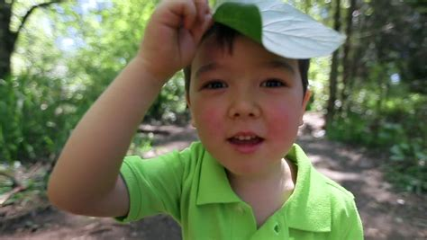 leaf boys model silly little asian boy places a big leaf on his head stock