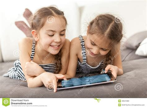 two girls having on couch portrait of two smiling girls lying on couch and using