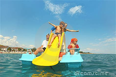 pedal boat yellow family on pedal boat with yellow slide in sea stock photos
