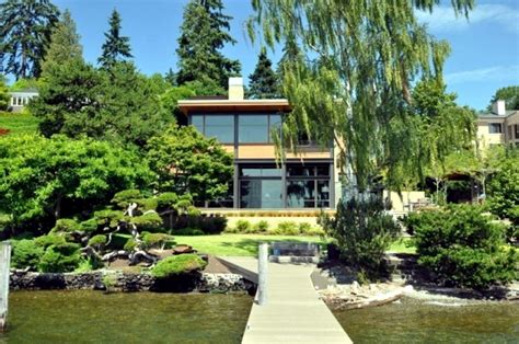 Modern house on the lake with a flat green roof and a