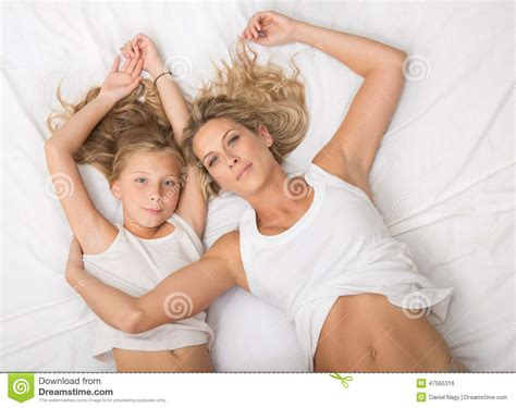 in bed with mom curly blonde mother and daughter lays on bed together