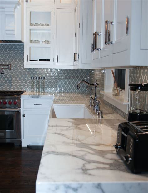 bluish grayish moroccan style tiles for the backsplash with calcutta marble countertops by mesa
