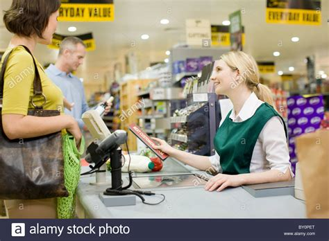 Checkout Register Cashier cashier and customers at supermarket checkout stock photo