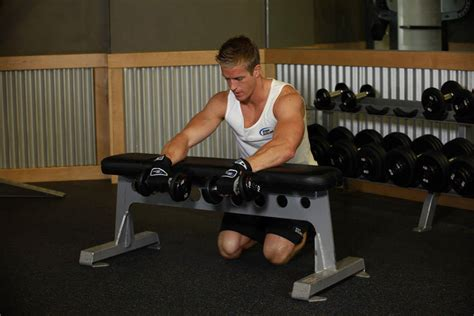 knee on bench dumbbell palms down dumbbell wrist curl over a bench exercise guide