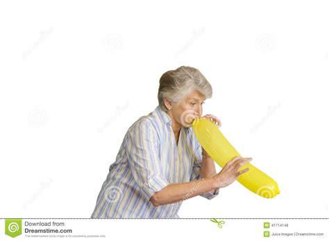 Senior woman blowing up yellow balloon cut out stock photo image 41714148