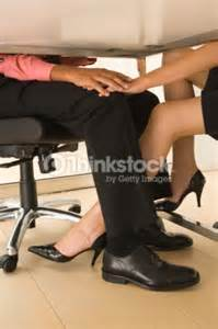 coworkers footsie table stock photo thinkstock