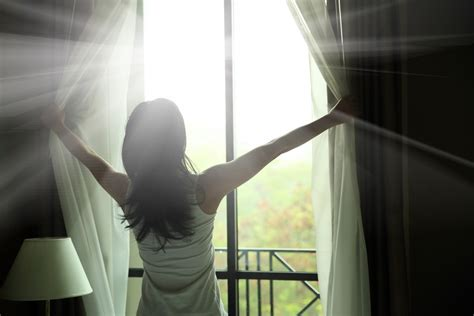 woman opening curtains adding dazzle to the everyday yoffie life