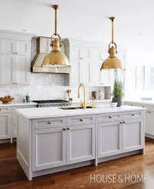 traditional kitchen with gray shaker cabinets brass