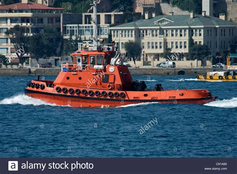 Tug Boat Shoppinf the orange marin tug boat of istanbul with tyre fenders around the stock photo royalty free