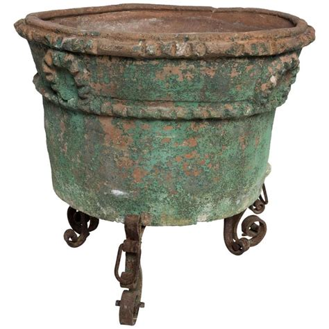 large painted terra cotta planter with a wrought iron