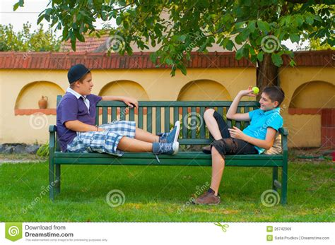 boys bench two teenage boys sitting on the bench and throwing royalty