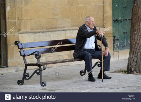 sitting on bench old man sitting on bench in ubeda spain stock photo