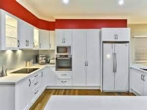 idei amenajari model de bucatarie alb cu nuante de rosu si parchet laminatmodel de bucatarie