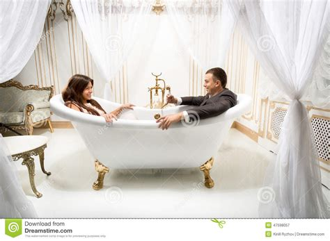 man and woman in bathroom clothed man and woman having fun in luxurious bath stock