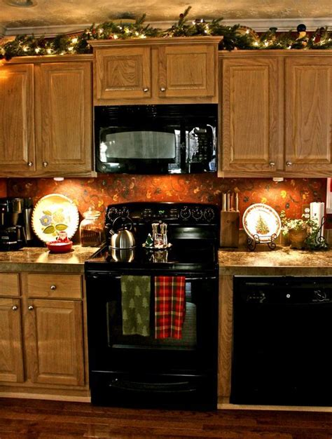 top of kitchen cabinet christmas decorating ideas christmas garland on plant shelves or above kitchen