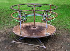 Vintage rusty merry go round abandoned playground stock photo