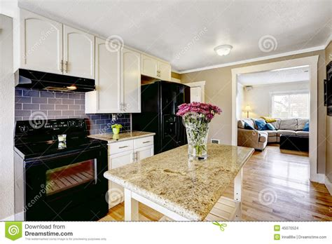 white kitchen island with black granite top kitchen island with granite top and flowers stock photo