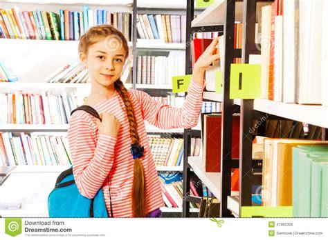 libro la ragazza con la la ragazza con la treccia sta lo scaffale per libri vicino in biblioteca immagine stock