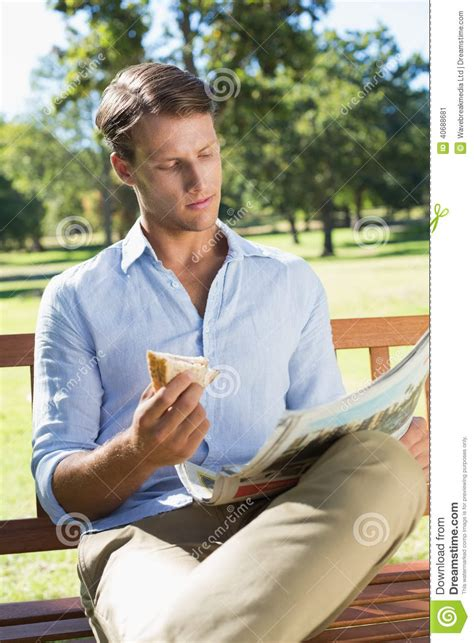 eating bench handsome man sitting on park bench eating sandwich and reading paper stock photo