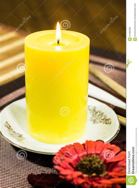 composizione di un fiore composizione di una candela gialla con un piatto bianco e