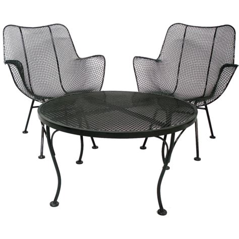 wrought iron and mesh table with four armchairs by woodard