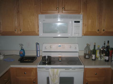 range hood with cabinet above white microve shelf above stove under oak kitchen cabinet