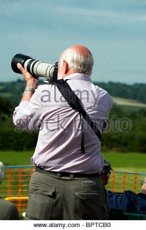male wildlife photographer using telephoto lens in bird
