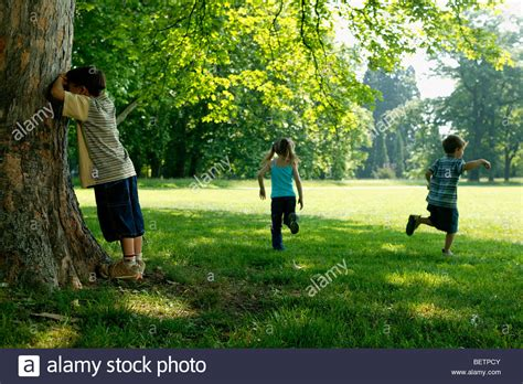 hide and seek three children hide and seek in the park stock photo royalty free image