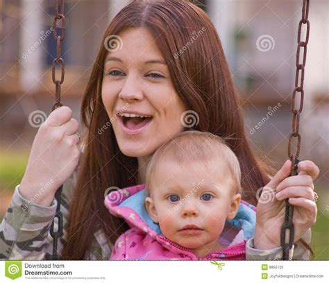 mom swings baby around young mother and baby daughter on swings royalty free