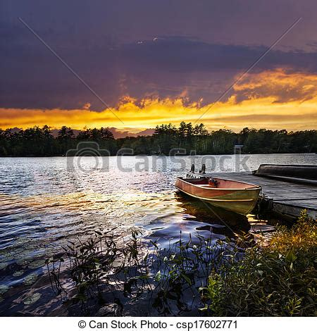 picture of boat docked on lake at sunset rowboat tied to