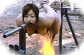 Asian Woman Roasted On A Spit Over Fire
