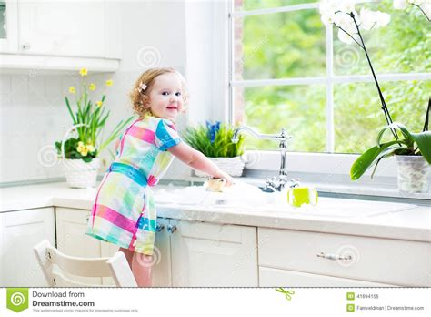 washing baby in kitchen sink toddler in colorful dress washing dishes stock