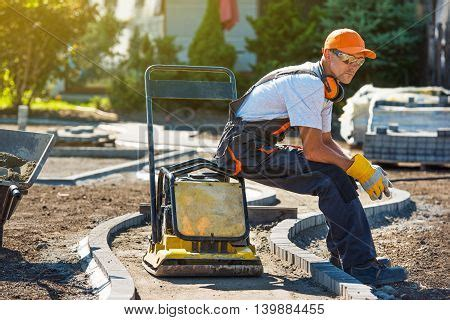 crating a while at work brick paver worker resting on his soil plate compactor while at work stock photo